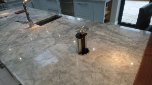 Quartzite worktop with pop up sockets, prep sink, inset compost bin with walnut lid by Celtica Kitchens
