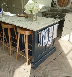 Kitchen island cabinetry by Celtica Kitchens with framed end panel, towel rail, knee-space with stools