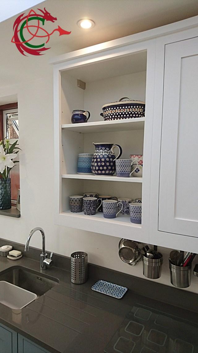 open shelf wall cabinet in painted shaker kitchen, quartz worktop, undermount sink, drainer grooves