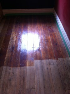 The difference is evident between the rough floorboards and the varnished ones.