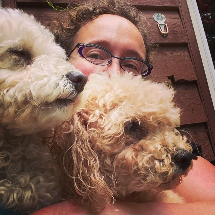 the author sits behind two toy poodles in profile; one white and one peach