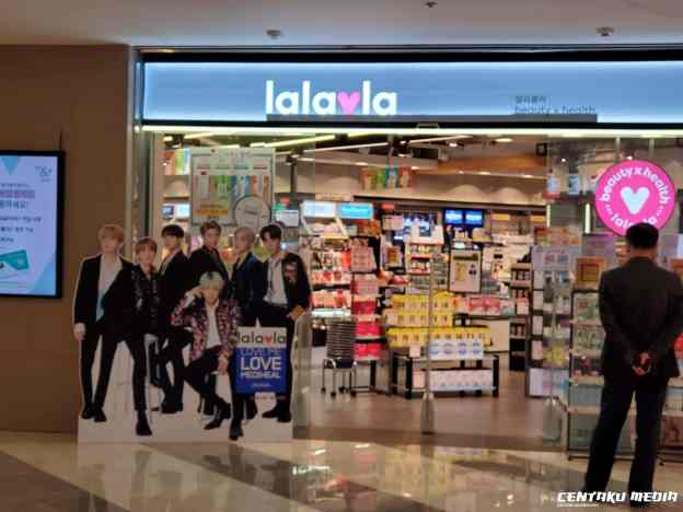 A pop-up poster featuring BTS stands in front of a Heath & Beauty store, Lalavla.