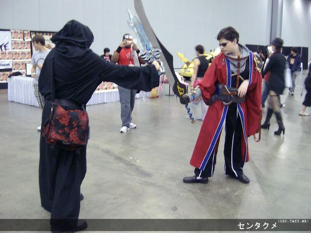 Sir Auron from Final Fantasy X engaging in a battle with another cosplayer.