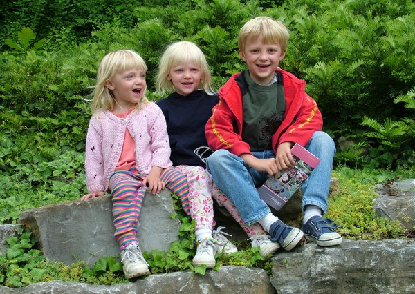 Three blonde haired school age siblings sitting on a rock