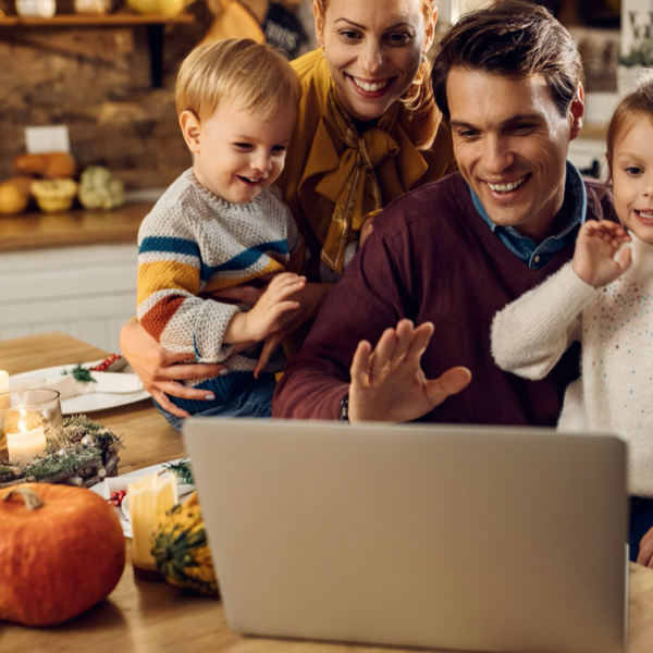 Family of 4 waving to someone on their computer.