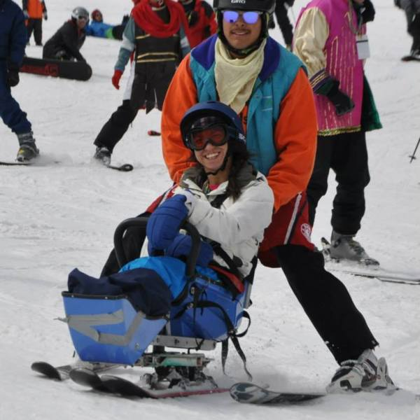 Angela West skiing in an adaptive wheelchair with assistance, both of them smiling.