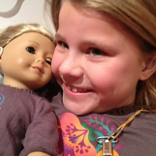 Girl using hearing aids holding a doll with hearing aids