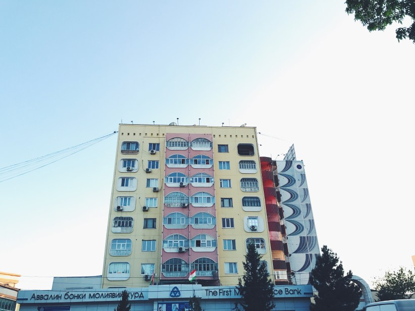 An old Soviet apartment building with windows shaped as the traditional Central Asian nomad home - a jurt