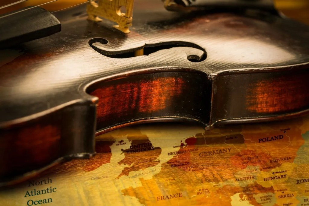 Barriers to music - a fiddle lying on a map of Euorpe