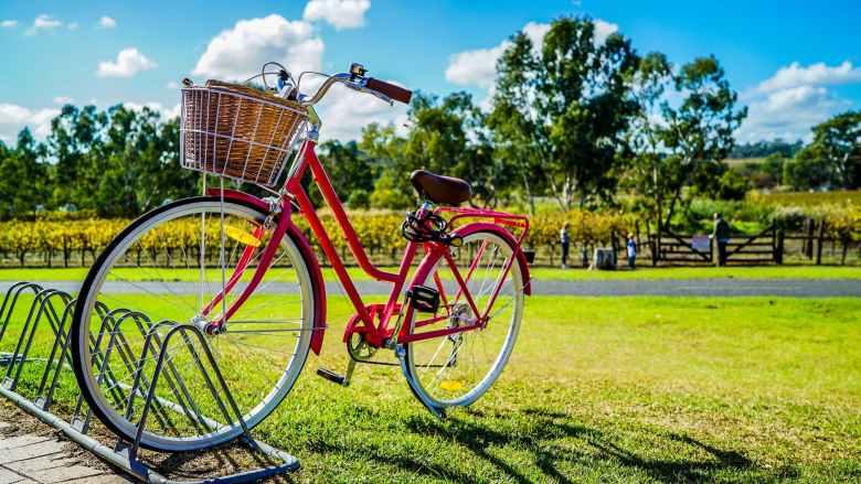 red cruiser bike parked on metal bike stand