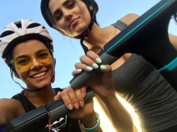 Two girls taking a selfie on electric scooters