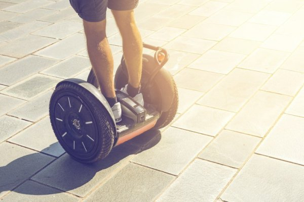 Man riding a Segway on a paved surface