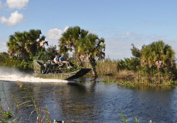 Duck hunters on an airboat on a river in Florida