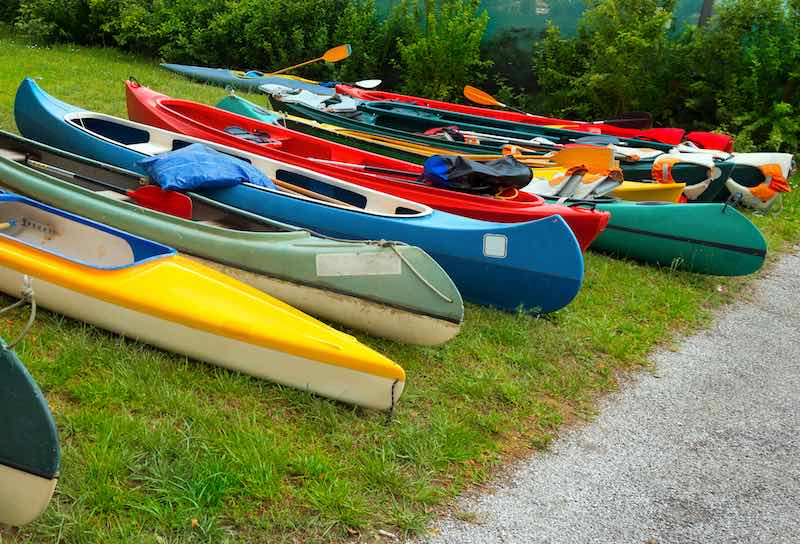 Different types of canoes an kayaks laying on the grass