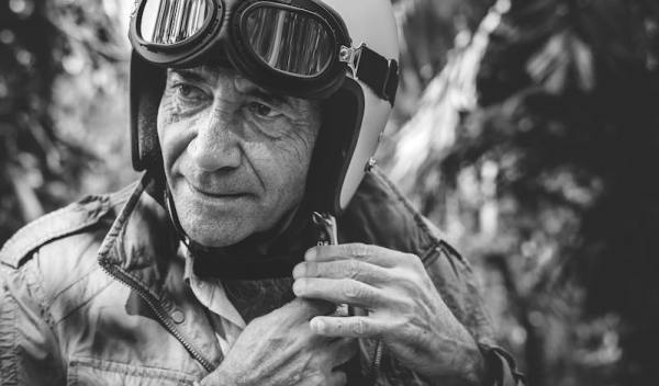 Black and white photo of an old biker wearing a retro vintage motorcycle helmet