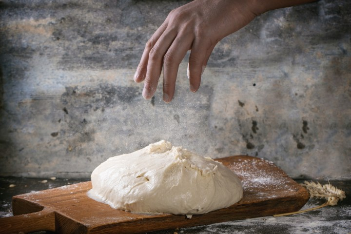 Hand reaching for bread dough