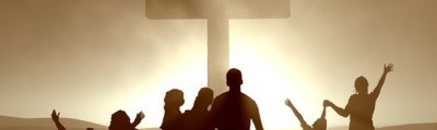 Group od people standing in front of a wooden cross with bright sunlight behind