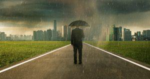 Man walking through storm with an umbrella