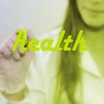 "Girl writing ""health"" on a glass screen"