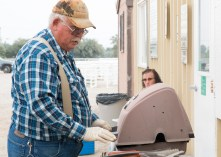 Mike Donelson makes hamburgers and hot dogs for the rodeo team.