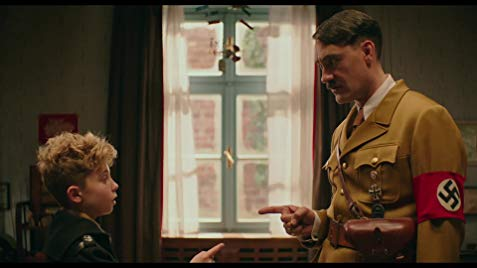 The image is a still from Jojo Rabbit, where Taika Waitit portrays Hilter and Roman Griffin Davis portrays Jojo (Image courtesy of IMDB).