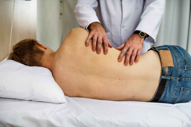 person massaging man while lying on bed
