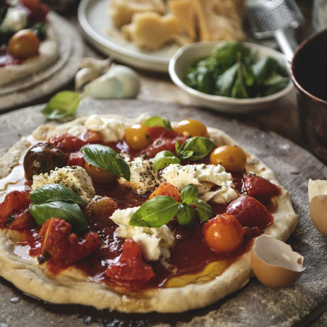 Primer plano de una pizza de queso, tomate y albahaca.