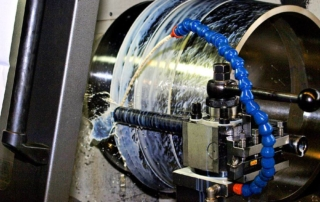An image of a metal lathe turning what looks like a wheel there a coolant pouring over the part as it cuts from a blue hose, it look kind of cool the way the fluid is captured in the still image.
