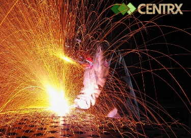 image of a man with a welding mask on keaning over a large metal part and welding, there are lots of sparks flying it looks really cool on a black background.