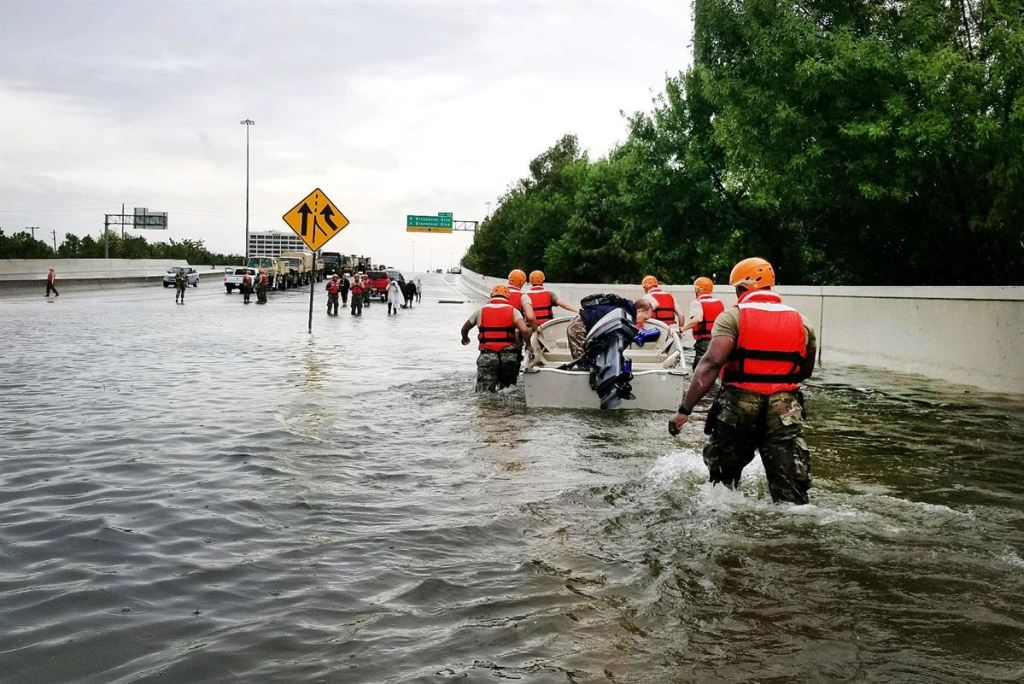 Texas National Guardsmen rescue a resident by boat during flooding caused by Hurricane Harvey in Houston