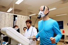 Man running on treadmill wih mask on, three persons are preforming a VO2 max test.