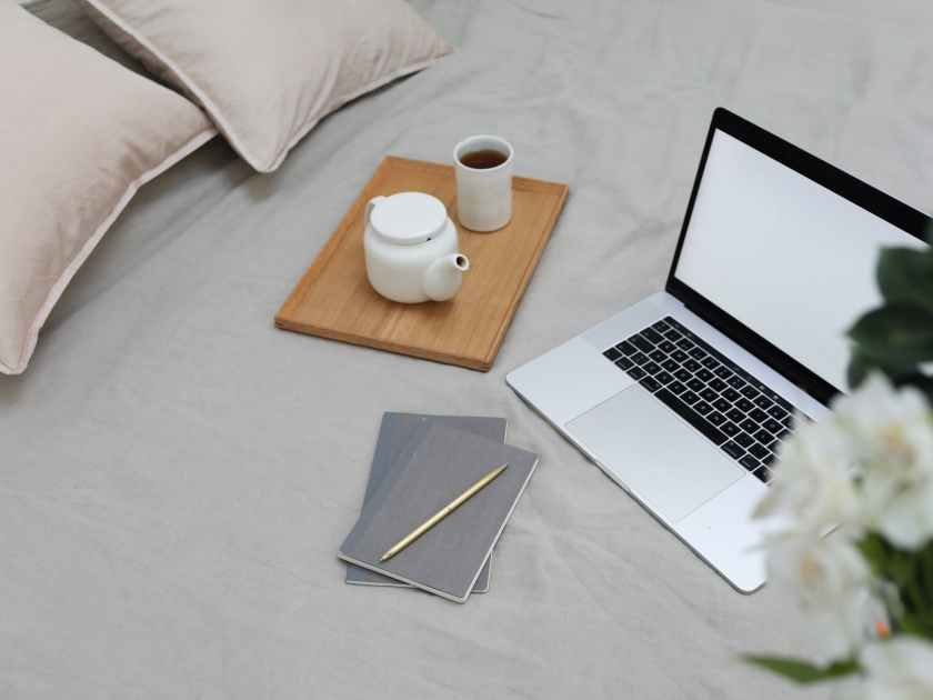 modern laptop with notebooks and pen arranged on bed with coffee pot and cup