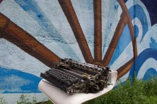 Eine alte Schreibmaschine auf einem Barhocker am Straßenrand vor einer Mauer