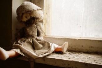 Eine schöne Puppe sieht aus dem Fenster in den Wald