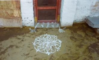 Rangoli - Mandala Muster auf dem gelb gefärbten Boden in Hampi