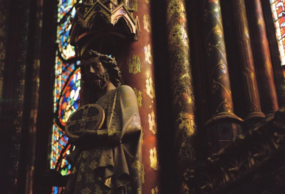 In der Sainte Chapelle fällt buntes Licht auf eine Heiligenfigur