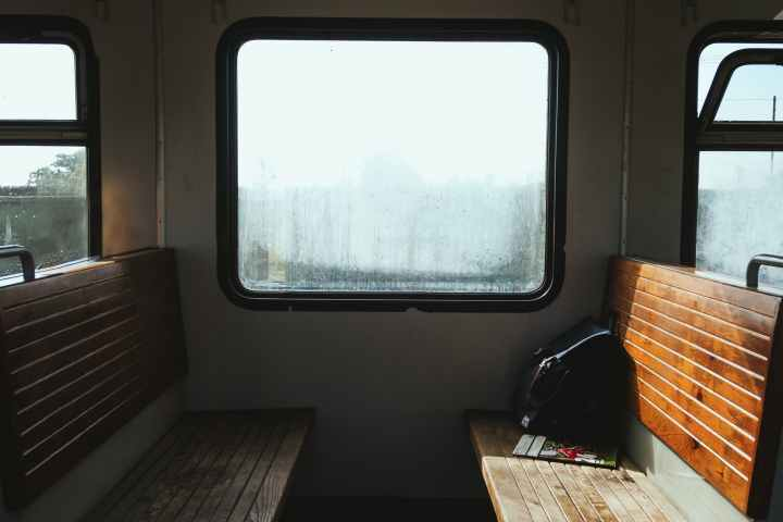 wooden benches with rucksack near window in train