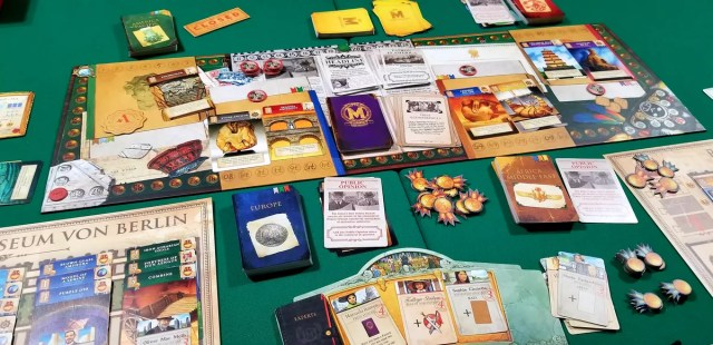 Shot of the Museum boardgame showing the different decks and pieces.