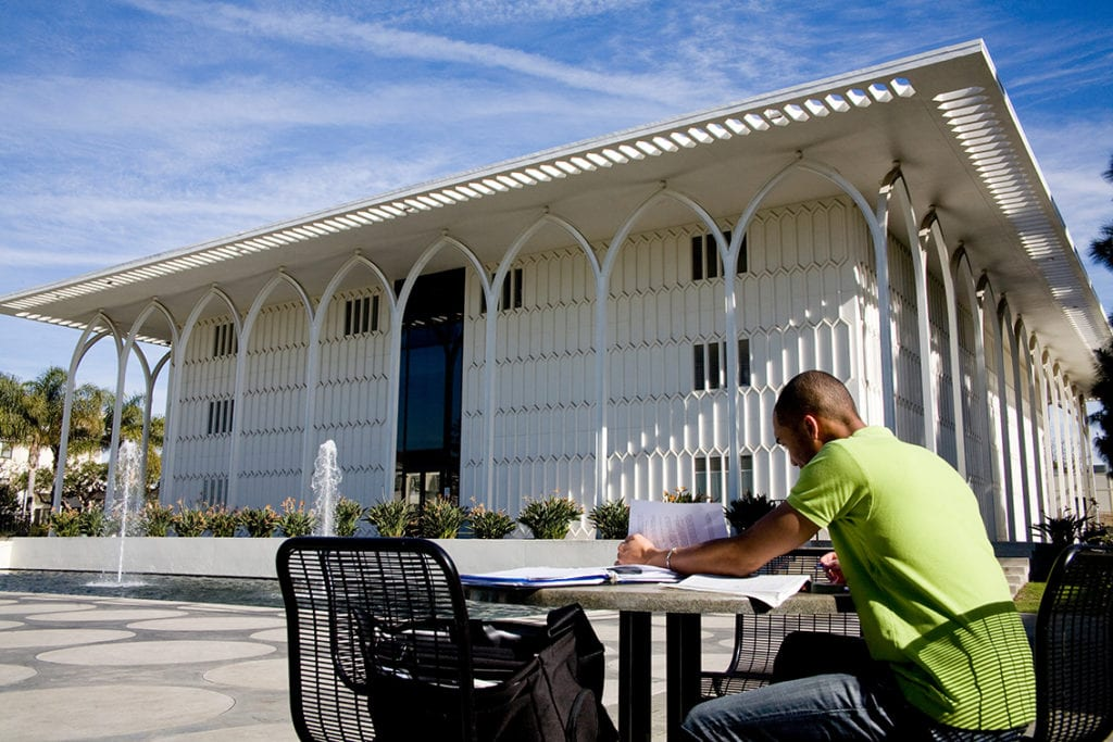Student studying in front of fountain