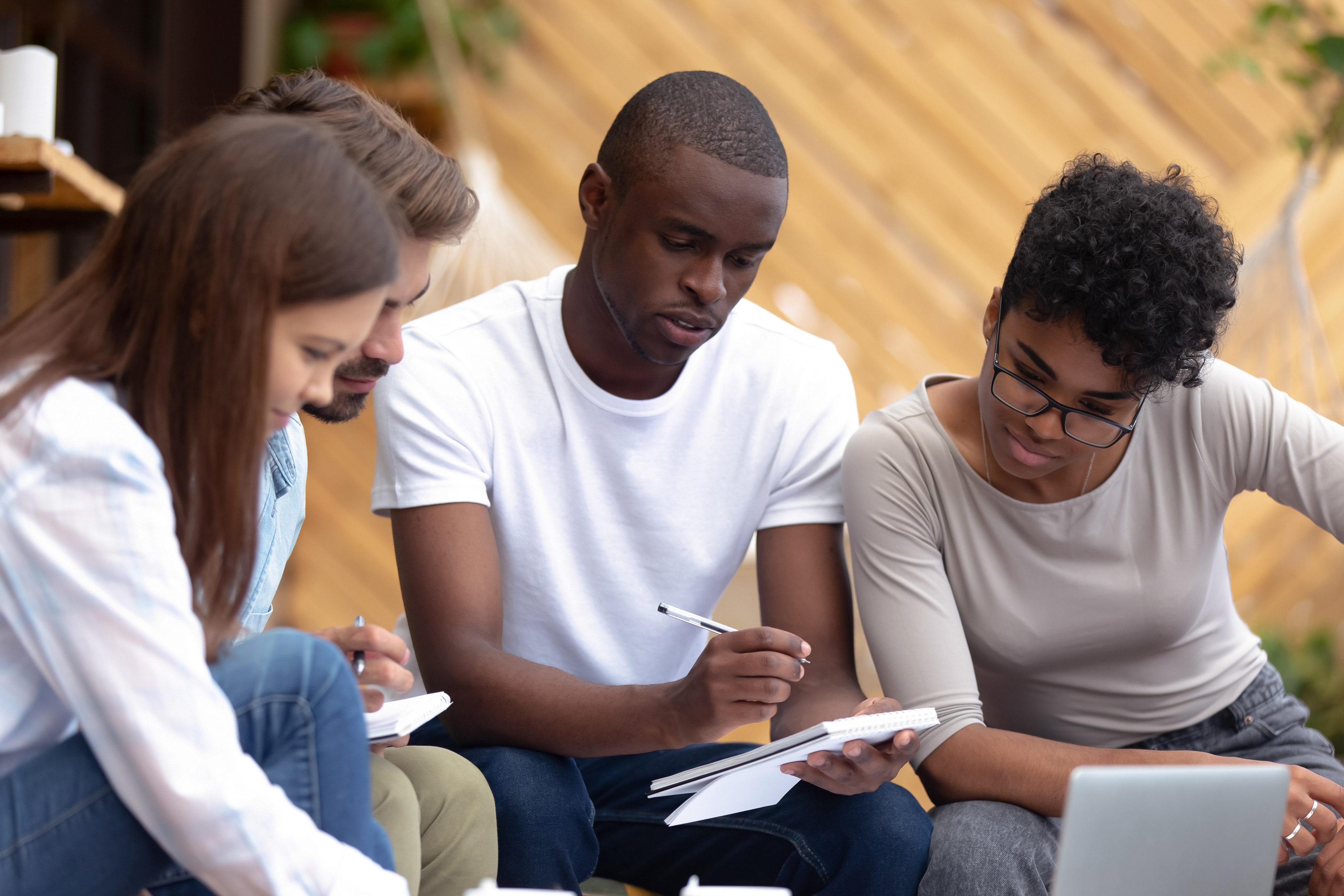 Beautiful smart girls handsome clever guys sitting in cozy place studying writing notes thoughts in notepad. Skilled man helps to teammates understand lecture learn preparing for examination together