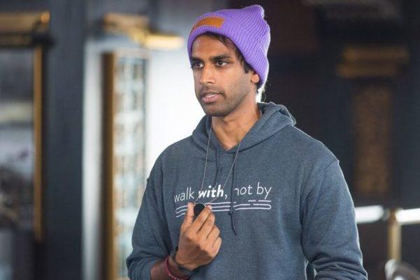 Jonathan Kumar in a hoodie and purple cap presenting