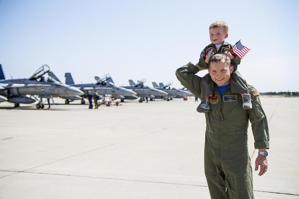 Todd Huber and son in front of fighter jets