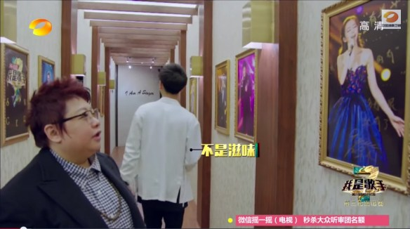 Meanwhile, in the halls of HunanTV headquarters, Han Hong examines a poster of Jane Zhang wearing a stunning white and gold dress.