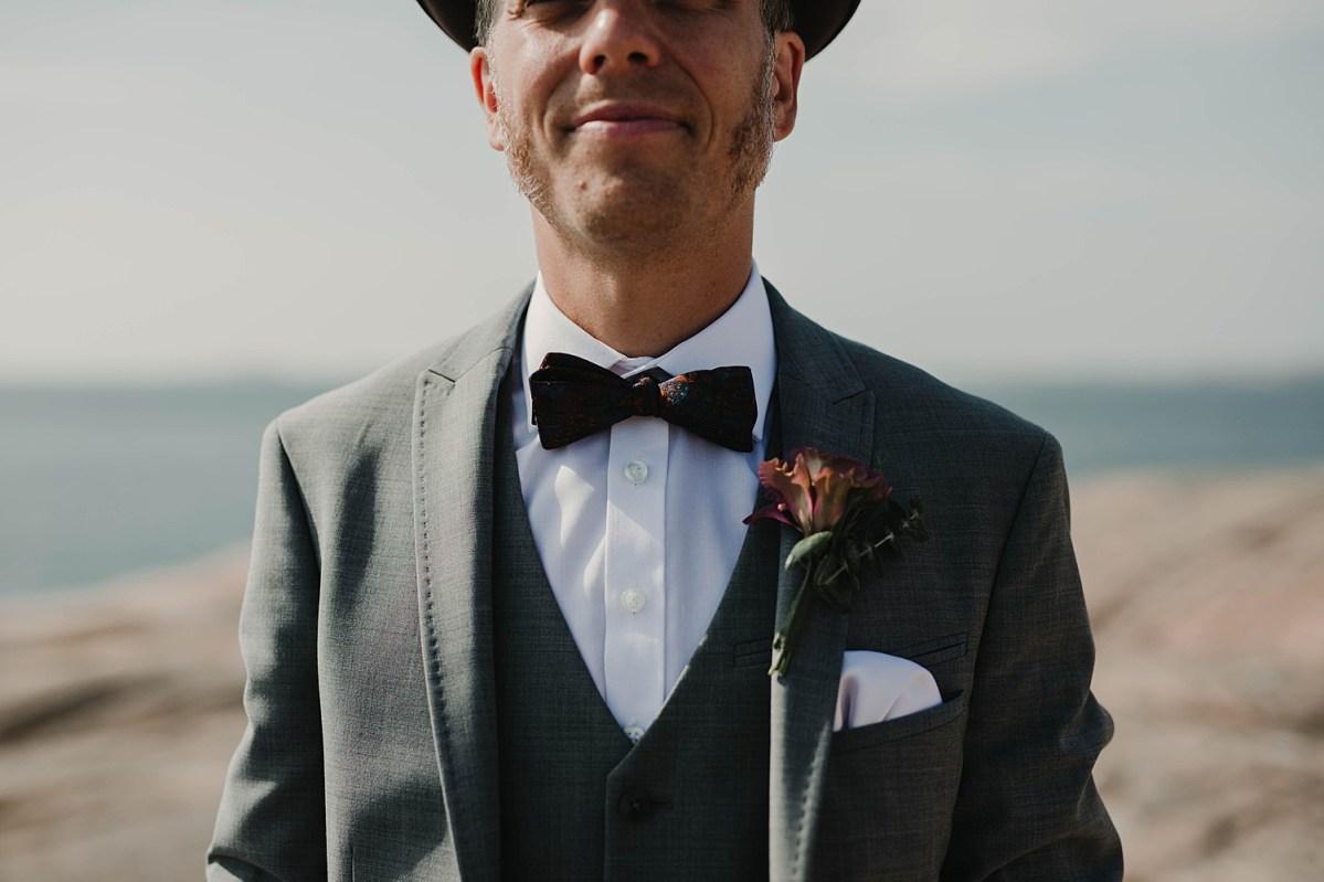 Detaljer bröllopsporträtt brudgum fluga hatt corsage