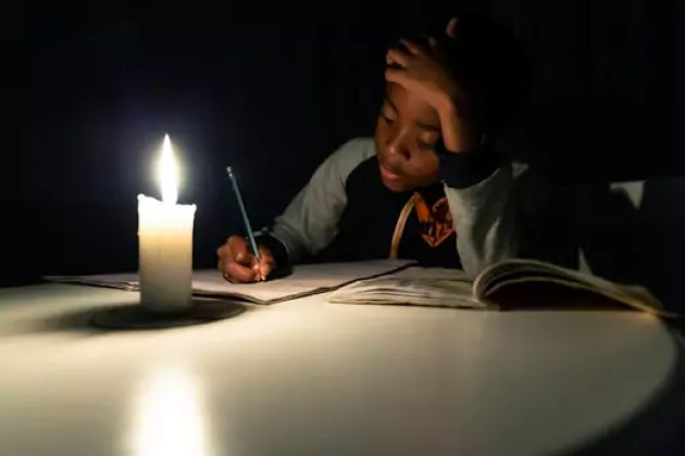 A Zimbabwean boy does his homework under candlelight in Harare.