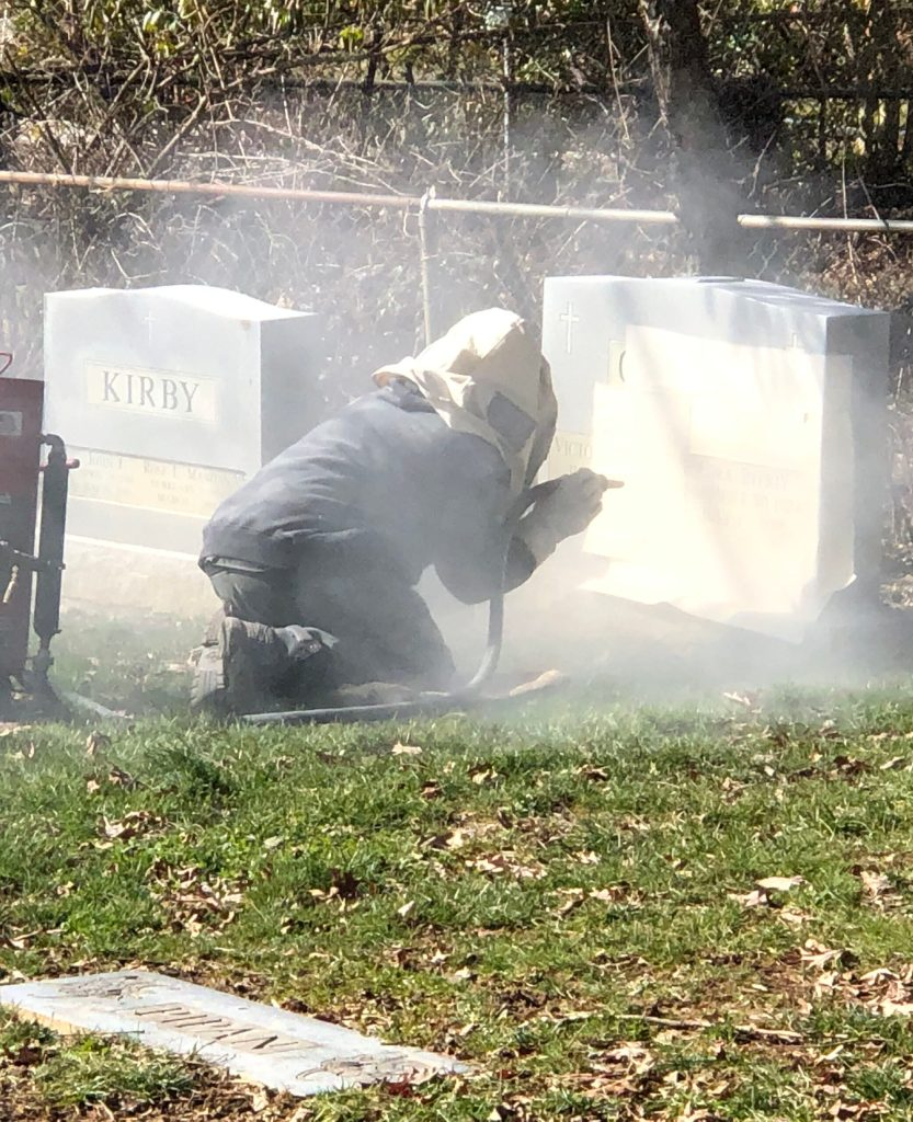 Sandblasting additional engraving onto headstone in the cemetery.