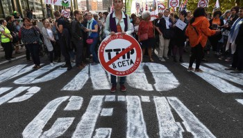 A woman holds a placard depicting a no entry sign with the TTIP and CETA logos, during a demonstration outside the European Union headquarters in Brussels, on September 20, 2016 to protest against huge transatlantic trade deals linking Europe with Canada and the United States. Several thousand The protests came after mass rallies in German cities on September 17, 2016 against the European Union's planned Transatlantic Trade and Investment Partnership (TTIP) with the United States, and the Comprehensive Economic and Trade Agreement (CETA) with Canada. / AFP PHOTO / JOHN THYS