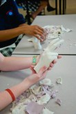 Students remove the cast of their hand from the mold.