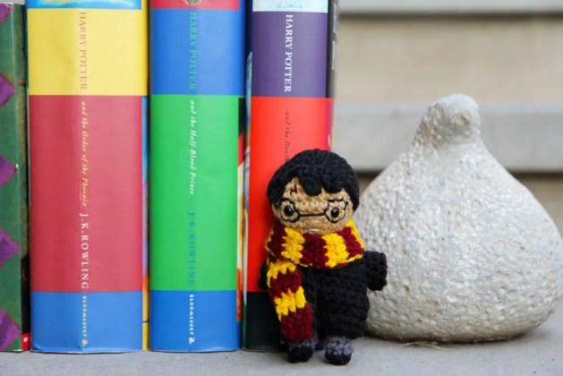 mini harry potter crochet doll standing in front of books