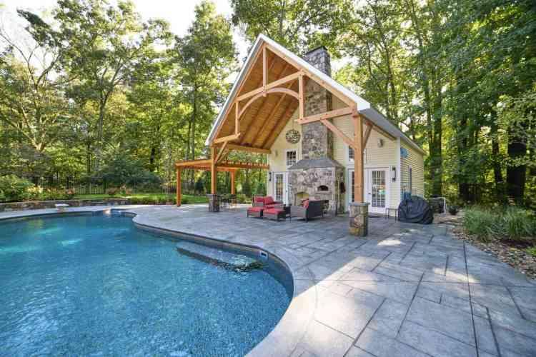 chalé super tradicional usado como casa de hóspedes, em frente a uma piscina.